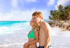 Pares rubios de turistas jovenes en una playa tropical Foto de archivo libre de regalías