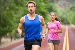 Pares running que movimentam-se na estrada Fotografia de Stock Royalty Free