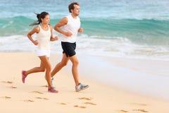 Pares running que movimentam-se na praia que exercita o esporte Fotografia de Stock
