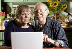 Pares sênior com um computador portátil Fotografia de Stock Royalty Free
