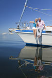 Pares sênior felizes na curva de um barco de vela Imagens de Stock Royalty Free