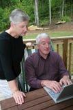 Pares sênior felizes no computador Fotografia de Stock Royalty Free