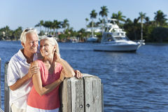 Pares sênior felizes por Rio ou por mar com barco Imagem de Stock Royalty Free
