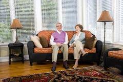 Pares sênior felizes que sentam-se no sofá da sala de visitas Imagens de Stock