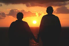 Pares sênior mais velhos que prestam atenção ao por do sol Imagem de Stock Royalty Free
