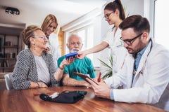 Pares sênior na discussão com o visitante da saúde em foto de stock royalty free