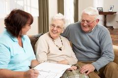 Pares sênior na discussão com visitante da saúde Foto de Stock Royalty Free