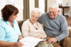 Pares sênior na discussão com visitante da saúde Foto de Stock