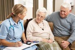 Pares sênior na discussão com visitante da saúde Fotos de Stock Royalty Free