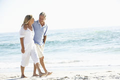 Pares sênior no feriado que anda ao longo da praia de Sandy foto de stock royalty free