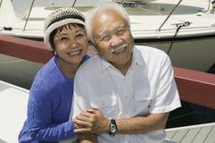 Pares sênior que abraçam no porto Fotografia de Stock Royalty Free