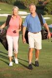 Pares sênior que andam ao longo do campo de golfe Fotografia de Stock Royalty Free