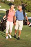 Pares sênior que andam ao longo do campo de golfe Imagens de Stock Royalty Free