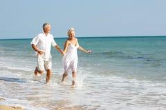 Pares sênior que apreciam o feriado da praia em The Sun Fotos de Stock