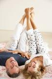 Pares sênior que encontram-se upside-down junto na cama imagens de stock royalty free