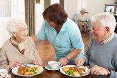 Pares sênior que estão sendo seridos a refeição por Equipa de tratamento Foto de Stock