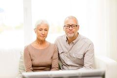 Pares sênior que prestam atenção à tevê em casa Fotos de Stock Royalty Free