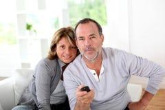 Pares sênior que prestam atenção à tevê em casa Foto de Stock Royalty Free