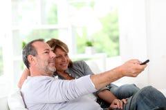 Pares sênior que prestam atenção à tevê em casa Fotografia de Stock