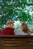 Pares sênior que sentam-se em um banco fotografia de stock royalty free