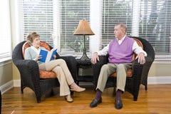 Pares sênior que sentam-se na leitura da cadeira da sala de visitas Fotografia de Stock Royalty Free