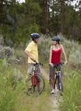Pares sanos en las bicis en un bosque Fotos de archivo