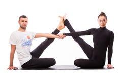 Pares sanos jovenes en la posición de la yoga respecto al fondo blanco Fotos de archivo