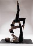 Pares sanos jovenes en la posición de la yoga respecto al fondo blanco Fotografía de archivo libre de regalías