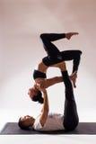 Pares sanos jovenes en la posición de la yoga respecto al fondo blanco Imagen de archivo libre de regalías