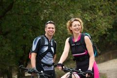Pares sanos que sonríen con las bicicletas Imagen de archivo