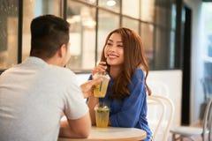 Pares satisfeitos que apreciam bebidas no café fotografia de stock