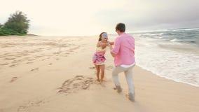 Pares saudáveis atrativos que têm o divertimento que corre junto na praia vídeos de arquivo