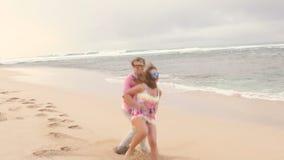 Pares saudáveis atrativos que têm o divertimento que corre junto na praia filme