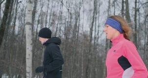 Pares saudáveis novos bonitos positivos que correm com o sportswear através da floresta na manhã do inverno vídeos de arquivo