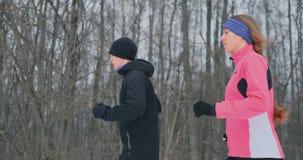 Pares saudáveis novos bonitos positivos que correm com o sportswear através da floresta na manhã do inverno filme
