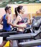 Pares saudáveis em uma escada rolante em um centro de esporte Imagens de Stock