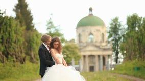 Pares sensuales del recién casado que abrazan feliz en parque con la iglesia antigua distante en el fondo metrajes