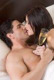 Pares sensuales jovenes cariñosos con Champán en cama Imagenes de archivo