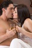 Pares sensuales jovenes cariñosos con Champán en cama Foto de archivo libre de regalías