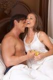 Pares sensuales jovenes cariñosos con Champán en cama Fotografía de archivo