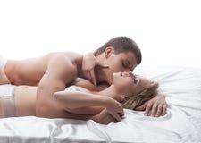 Pares sensuales que plantean besarse en cama Imágenes de archivo libres de regalías