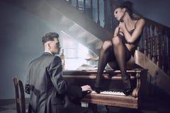 Pares 'sexy' em uma situação intimate com piano Imagem de Stock Royalty Free