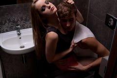 Pares 'sexy' no toalete, enganando ao redor Fotos de Stock Royalty Free