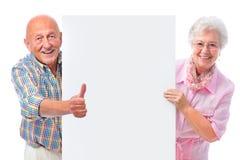 Pares sênior de sorriso felizes com uma placa em branco Fotografia de Stock Royalty Free