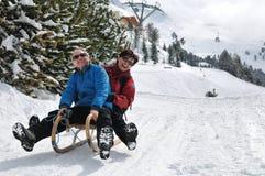Pares sênior no sledge que tem o divertimento Imagens de Stock Royalty Free