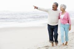 Pares sênior que andam ao longo da praia junto Imagem de Stock