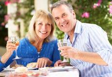 Pares sênior que apreciam a refeição ao ar livre Fotografia de Stock Royalty Free