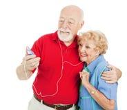 Pares sênior que escutam MP3s Fotos de Stock Royalty Free