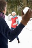 Pares sênior que têm a luta do Snowball na neve Fotografia de Stock Royalty Free