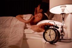 Pares soñolientos en cama con la mano que extiende al despertador en el m Imágenes de archivo libres de regalías